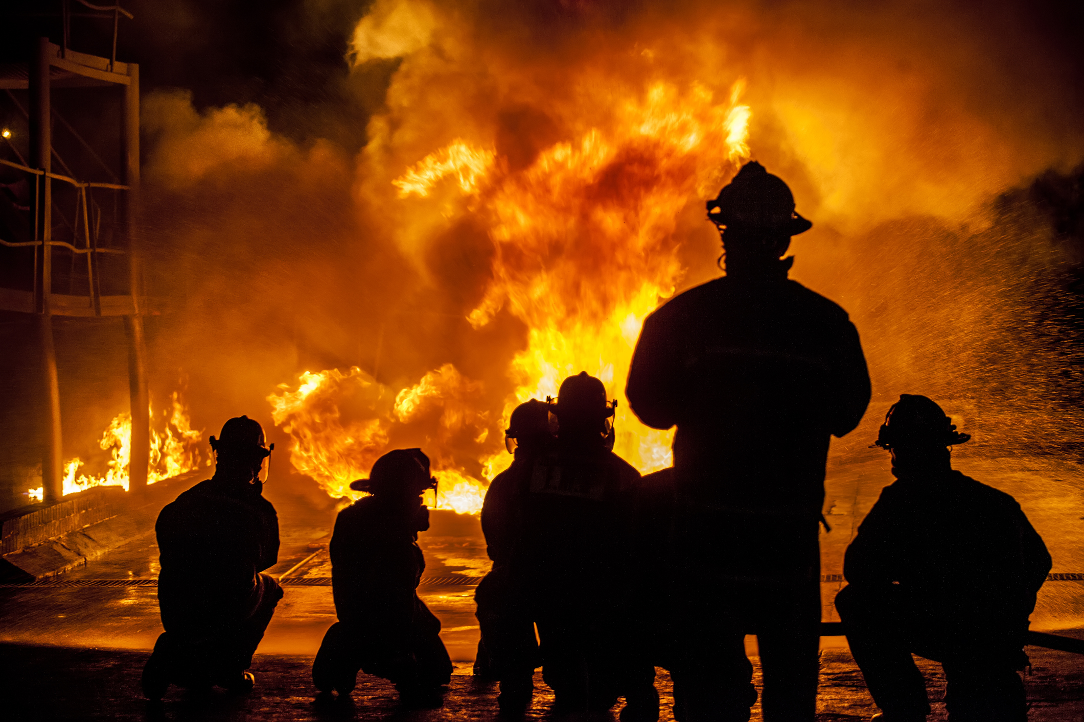 photo of firefighters silhouettes in front of blazing fire at night